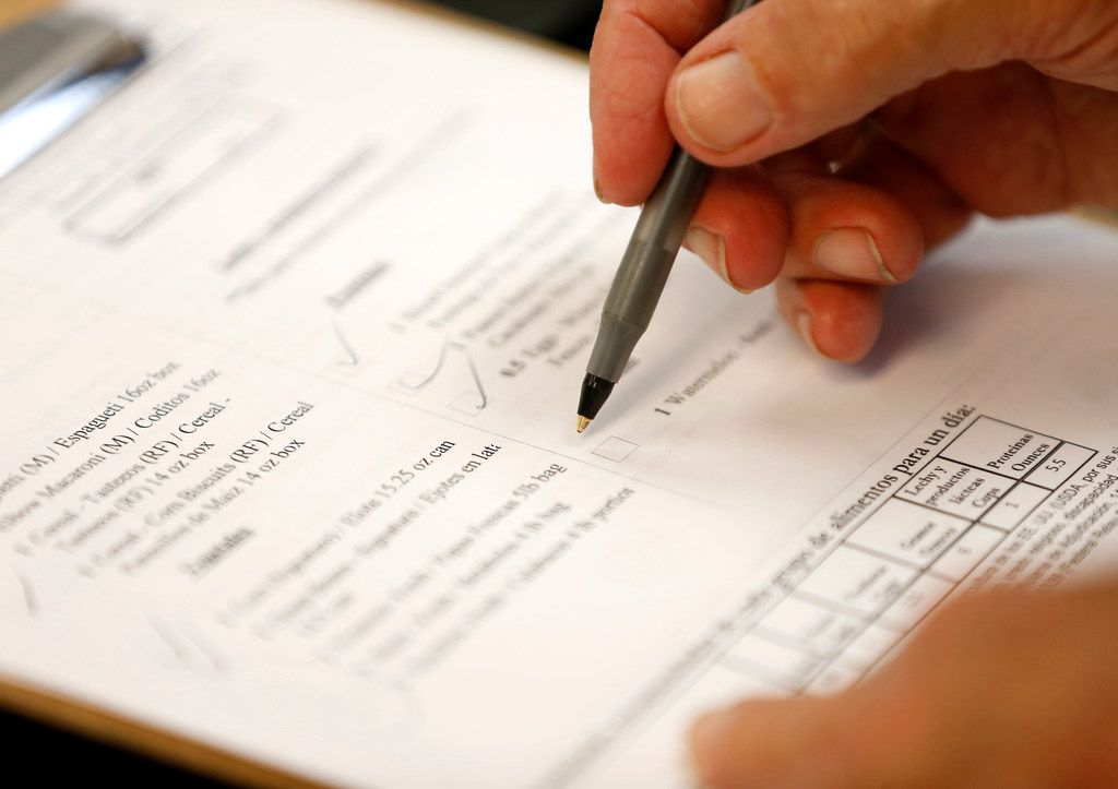 A volunteer goes through a check-list of items a client needs at Crossroads Community Services.