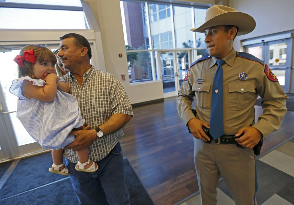New trooper Ernesto DeLaPena (right) watches his father-in-law Rudy Renteria (center) and niece Emily Huwel, 2, during the Texas Department of Public Safety graduation ceremony at Shoreline Church on Friday, June 17, 2016, in Austin, Texas. DPS has the highest number of Hispanic trooper graduates at any time over the last decade and currently the classes of this year are about 40 percent Hispanic.