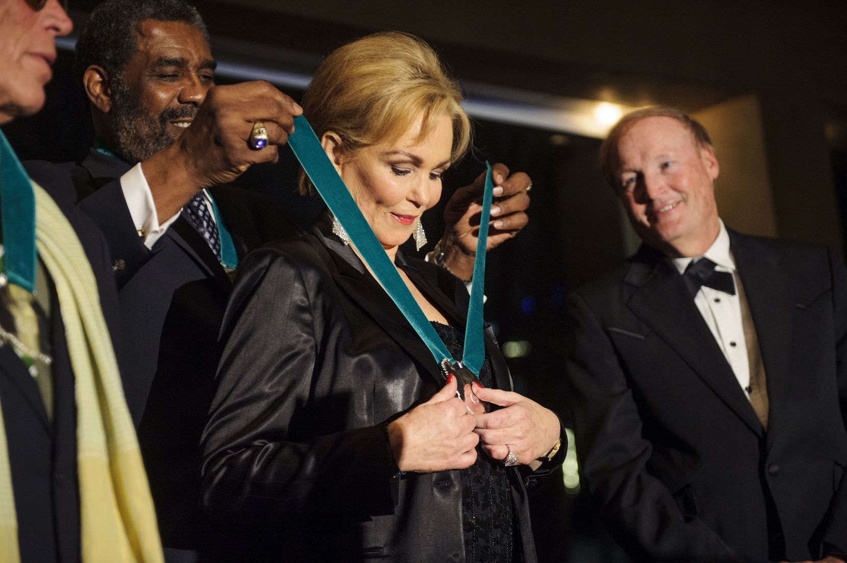 """Pittsburgh Steelers great """"Mean"""" Joe Greene presented George, a University of North Texas alumna, her medallion during the 2014 Emerald Eagle Honors ceremony at Dallas' Meyerson Symphony Center."""