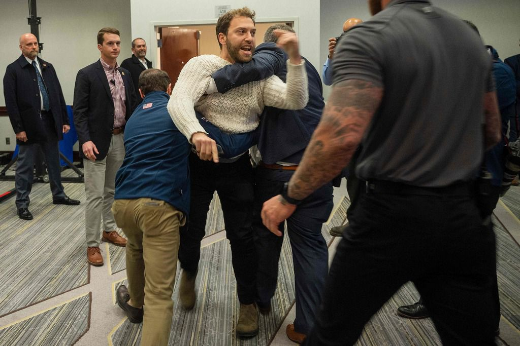 """A protester is dragged from the room as Donald Trump Jr. speaks  during a """"Keep Iowa Great"""" press conference in Des Moines on February 3, 2020."""