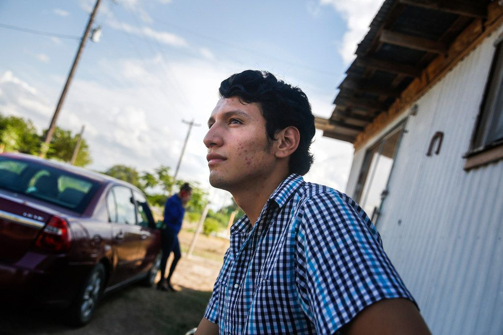Francisco Galicia waits outside his family's home as a television journalist sets up a camera and lights in the family's living room.