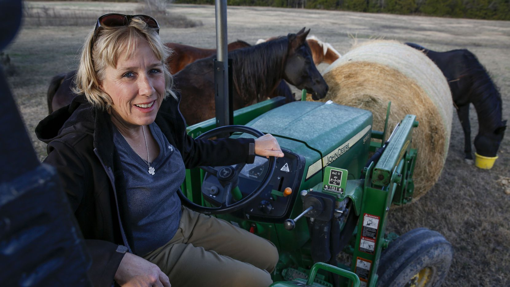 Brenda Rizos poses while moving a bale of hay around with a tractor surrounded by horses on her property in Lucas, Texas. Brenda, parent activist in Lovejoy ISD, has won a huge case against the district with the Texas Ethics Commission.
