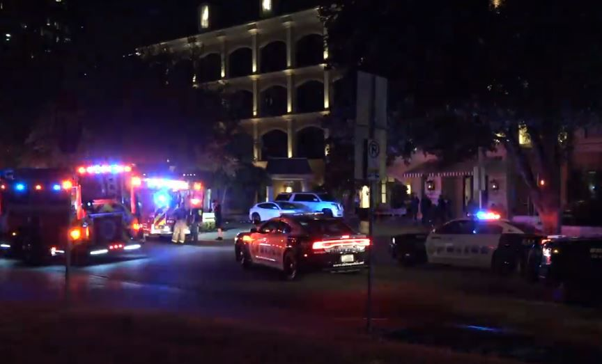 Dallas police and fire vehicles sit outside the Hotel ZaZa, where a woman was killed in a shooting Monday night.