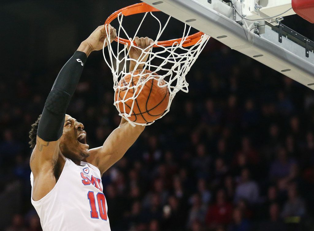 Southern Methodist Mustangs guard Jarrey Foster (10) dunks the ball over UCF Knights center Tacko Fall (24) in the first half of an NCAA basketball game between University of Central Florida and SMU at Moody Coliseum on the campus of Southern Methodist University in Dallas Wednesday December 27, 2017. Southern Methodist Mustangs led 26-21 at the half. (Andy Jacobsohn/The Dallas Morning News)