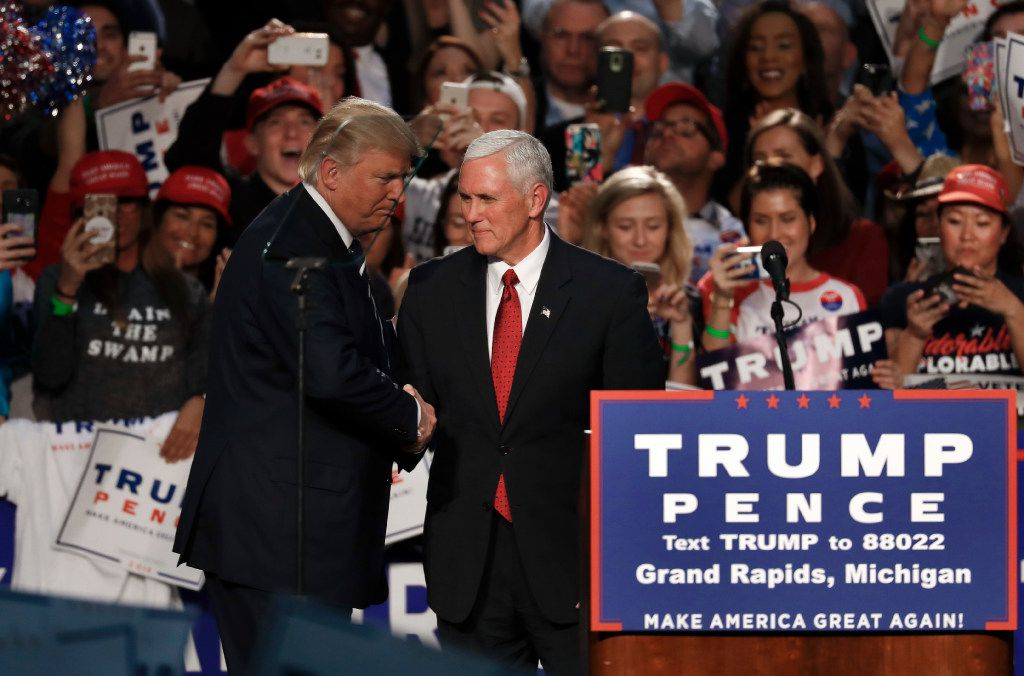 Republican presidential candidate Donald Trump shakes hands with vice presidential nominee, Indiana Gov. Mike Pence at a campaign rally in Grand Rapids, Mich., Tuesday, Nov. 8, 2016. (AP Photo/Paul Sancya)