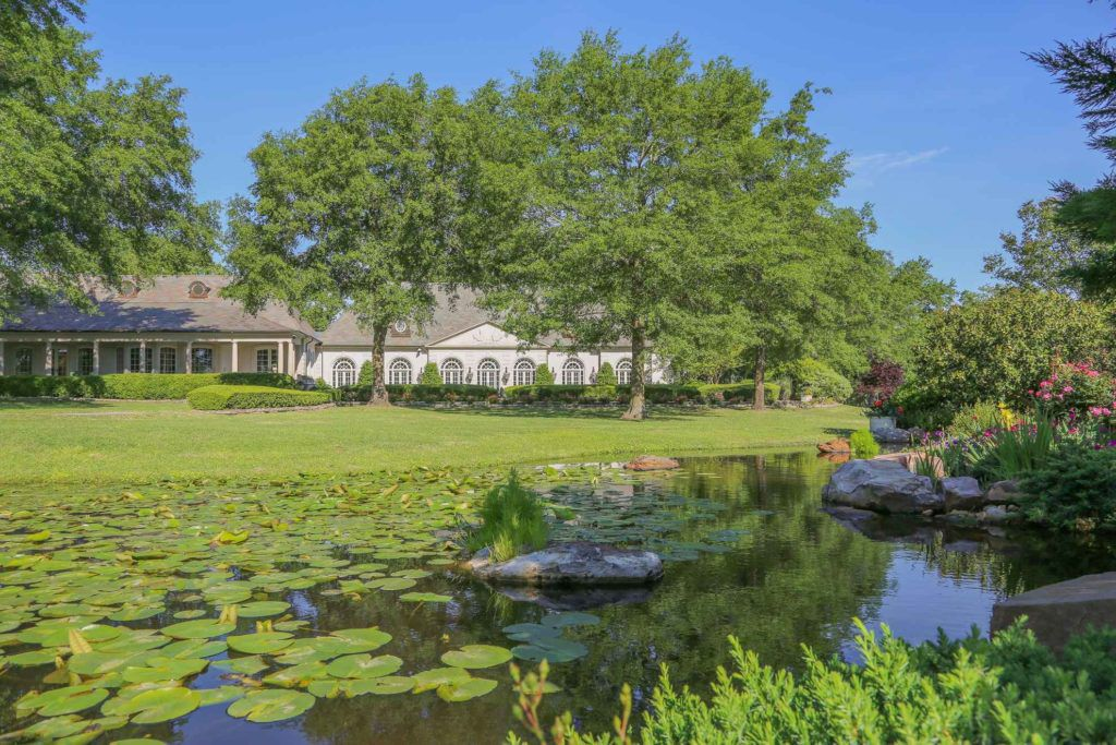 The house sits on landscaped grounds with ponds and swimming pools.