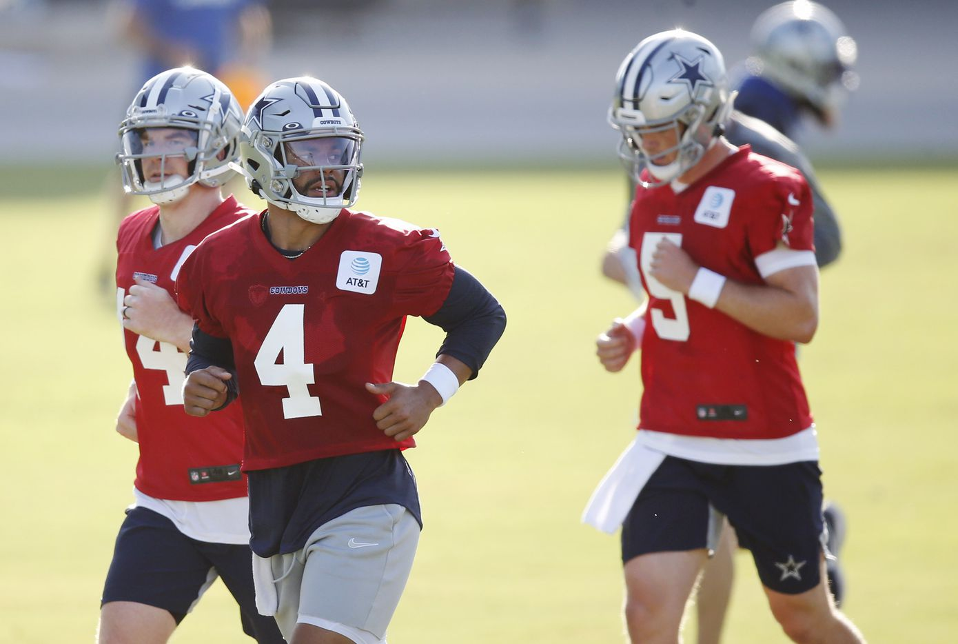 Dallas Cowboys quarterback Dak Prescott (4), Dallas Cowboys quarterback Andy Dalton (14) and Dallas Cowboys quarterback Clayton Thorson (5) take the field during the first day of training camp at Dallas Cowboys headquarters at The Star in Frisco, Texas on Friday, August 14, 2020. (Vernon Bryant/The Dallas Morning News)