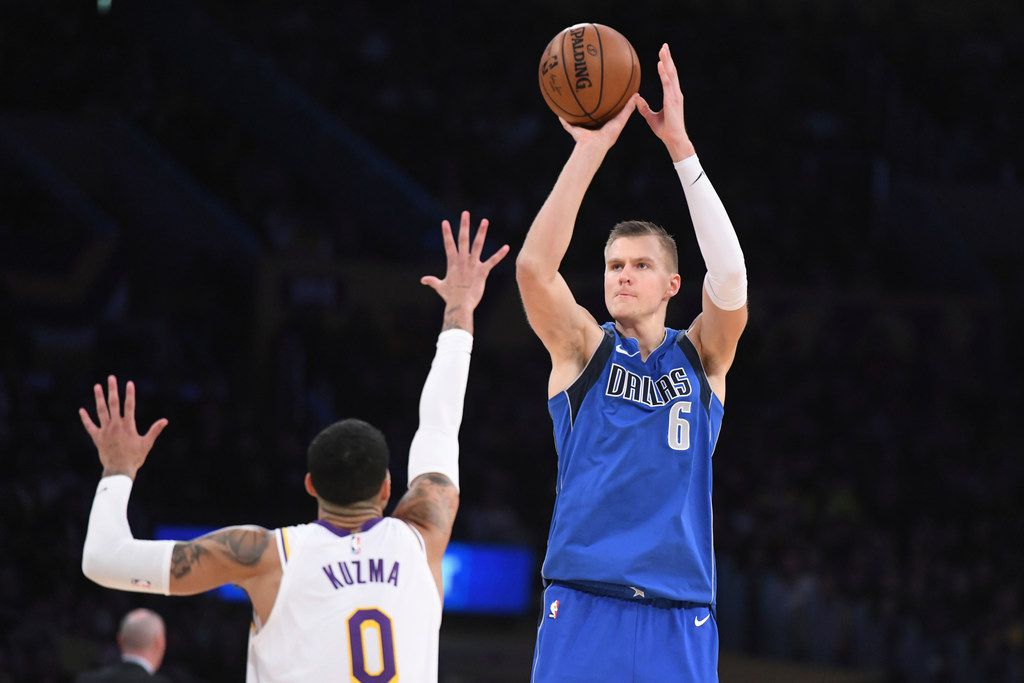 Dallas Mavericks forward Kristaps Porzingis (6) shoots over Los Angeles Lakers forward Kyle Kuzma during an NBA basketball game Sunday, Dec. 29, 2019, in Los Angeles.