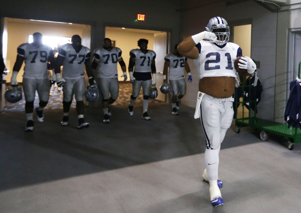 """Dallas Cowboys offensive guard Joe Looney (73) makes his way to the field in a Dallas Cowboys running back Ezekiel Elliott (21) jersey and gesturing the """"feed me,"""" motion as more of the offensive line laugh behind him prior to practice during training camp at The Star in Frisco on Tuesday, August 22, 2017. (Vernon Bryant/The Dallas Morning News)"""