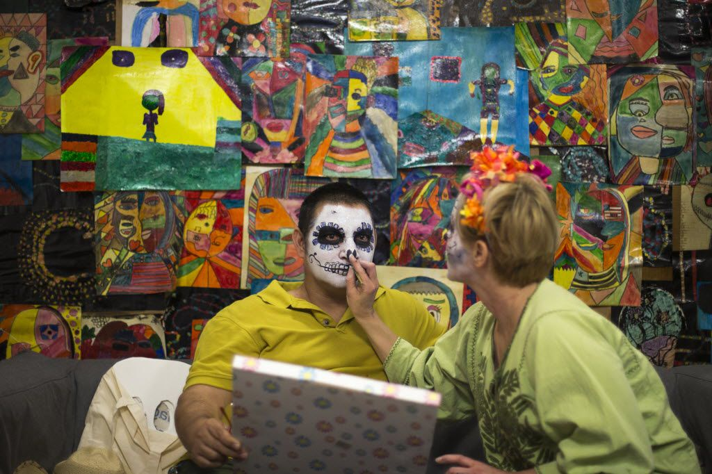 Alfredo Herrera, left, has his face painted during a Dia de los Muertos celebration in 2015 at Trans.lation: Vickery Meadow in Dallas.