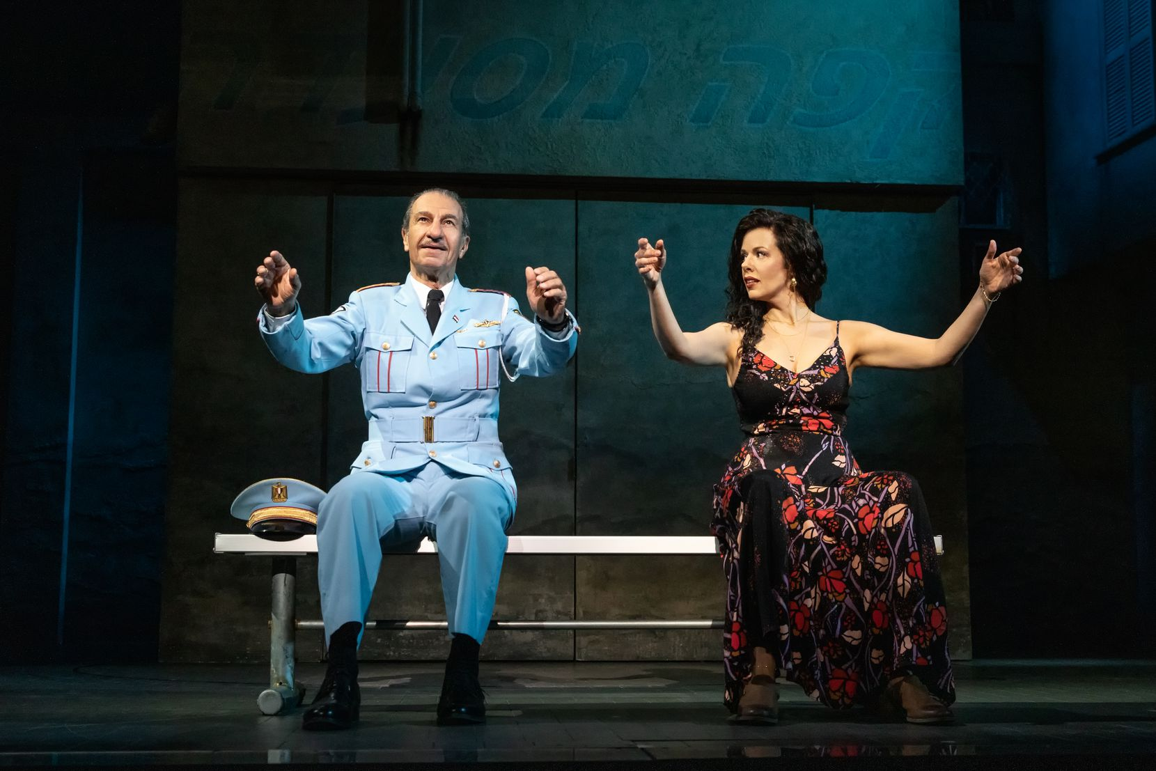 """Col. Tewfiq Zakaria (Sasson Gabay) and cafe owner Dina (Janet Dacal) hit it off in the Tony Award-winning musical """"The Band's Visit."""" In this scene, he shows her how he conducts. The North American touring production is at the Winspear Opera House, co-presented by Dallas Summer Musicals and the AT&T Performing Arts Center."""