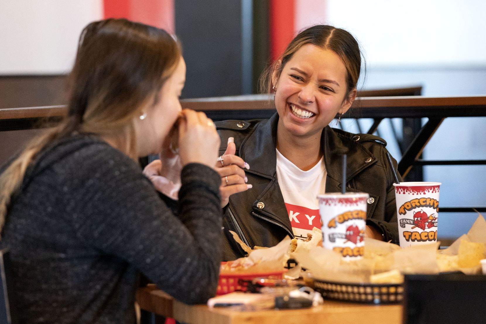 Jessica Molina (right) laughs with her sister Marisa Molina as they share a meal at Torchy's Tacos in Irving.