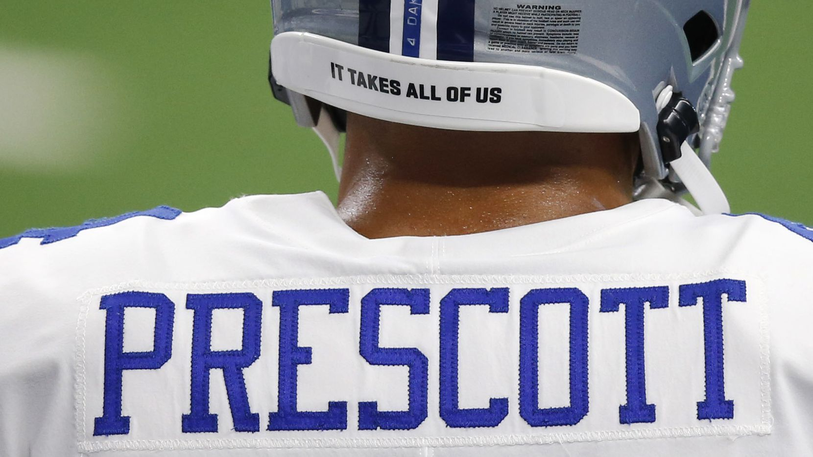 """The message """"It takes all of us,"""" printed on the back of the helmet of Cowboys quarterback Dak Prescott (4), is seen during pregame activities for the home opener against the Falcons at AT&T Stadium in Arlington on Sunday, Sept. 20, 2020."""