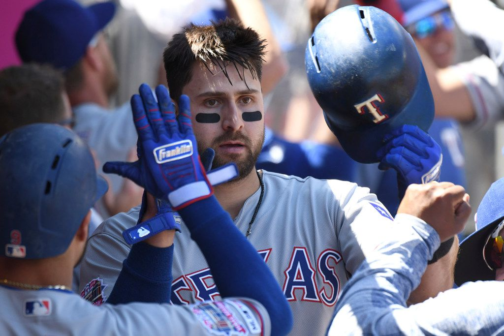Texas Rangers' Joey Gallo, center, is greeted in the dugout after hitting a two-run home run against the Los Angeles Angels during the second inning of a baseball game Sunday, April 7, 2019, in Anaheim, Calif. (AP Photo/Michael Owen Baker)
