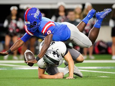 Arlington Martin quarterback Zach Mundell fumbles as he is hit by Duncanville linebacker Jadarius Thursby (8) during the first half of a Class 6A Division I Region I semifinal playoff football game at AT&T Stadium on Friday, Nov. 29, 2019, in Arlington. Duncanville recovered the fumble and returned it for a touchdown.
