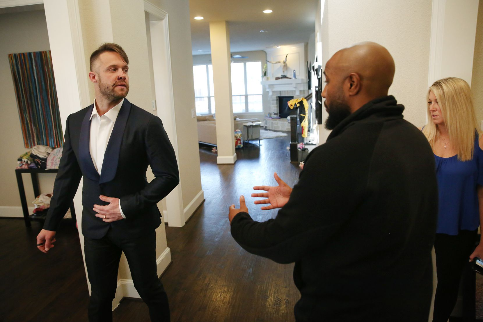 With scars on his face from a recent dog attack, David Vobora (left) preps for speaking engagements by getting fitted for a tux, with the help of bespoke concierge Jason Smith and David's wife, Sarah Vobora, at his home in The Colony.