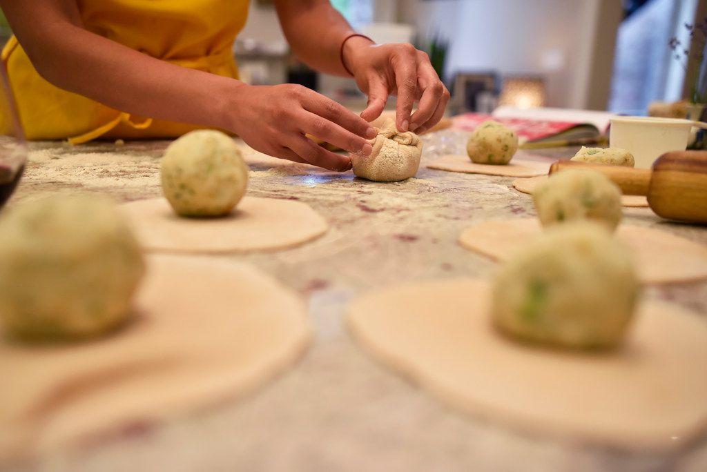 Food writer Priya Krishna rolls and folds dough while preparing paratha.