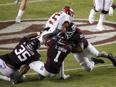 COLLEGE STATION, TEXAS - OCTOBER 31: Rakeem Boyd #5 of the Arkansas Razorbacks is tackled by Buddy Johnson #1 and Jayden Peevy #92 of the Texas A&M Aggies in the third quarter at Kyle Field on October 31, 2020 in College Station, Texas.