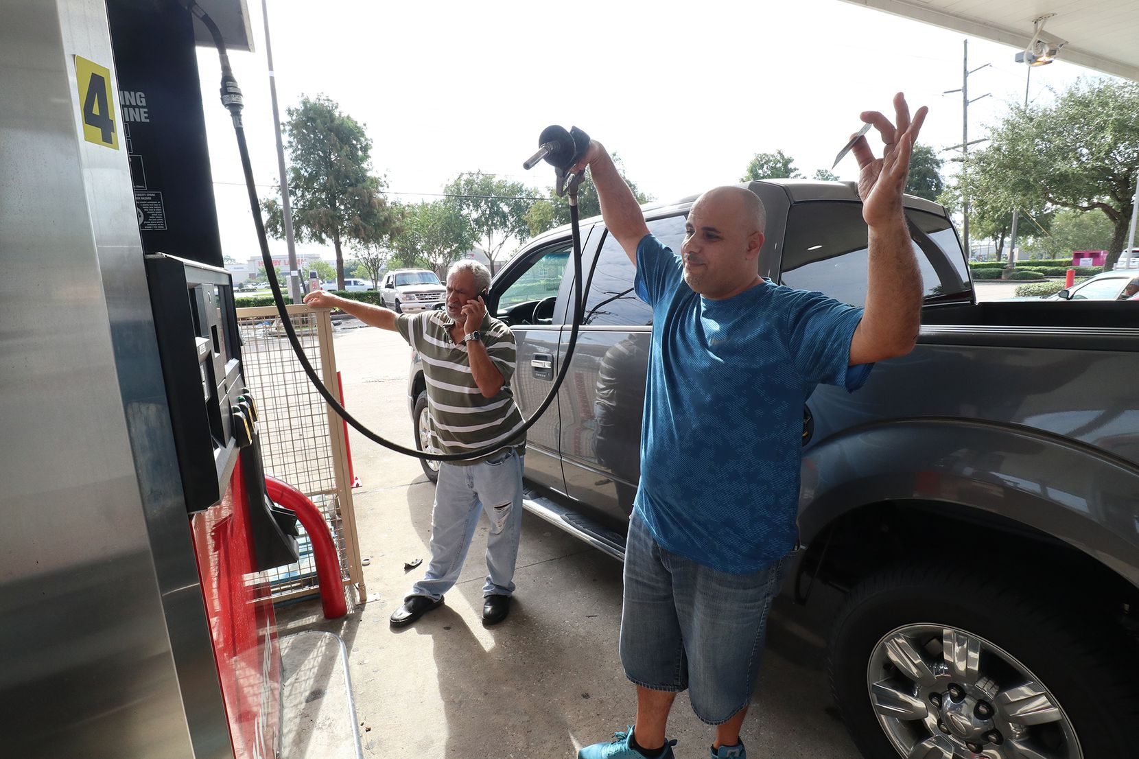 Rami Khdeir reacts to the gas pumps running out of fuel at Kroger in Beaumont, Texas,  August 31, 2017. His father-in-law Asad Bassa tries to find another place for fuel.