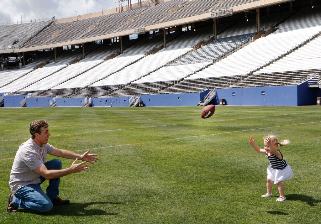 Michael Meredith, an American independent film director, screenwriter and producer, son of Cowboys great Don Meredith, left, plays catch with his daughter, Marlowe, 2, at the Cotton Bowl in Fair Park in Dallas on Tuesday, June 13, 2017. Michael is working on a documentary about the 1960s Cowboys when his Dad played quarterback. (David Woo/The Dallas Morning News)