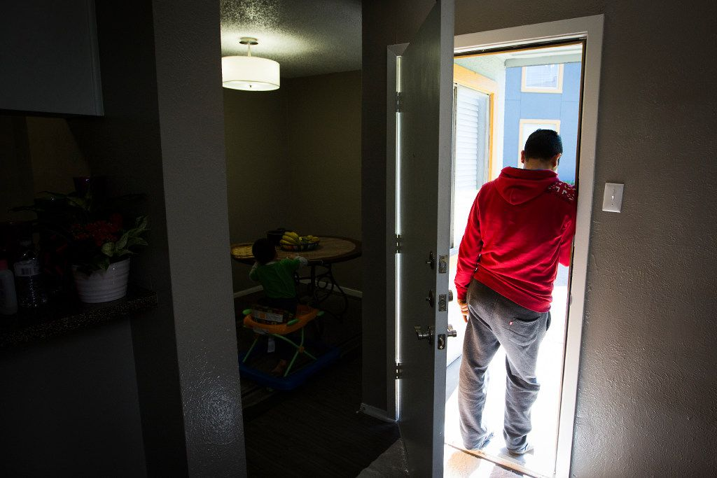 Moustafa Jawish waits in the doorway of his apartment for the arrival of his parents.