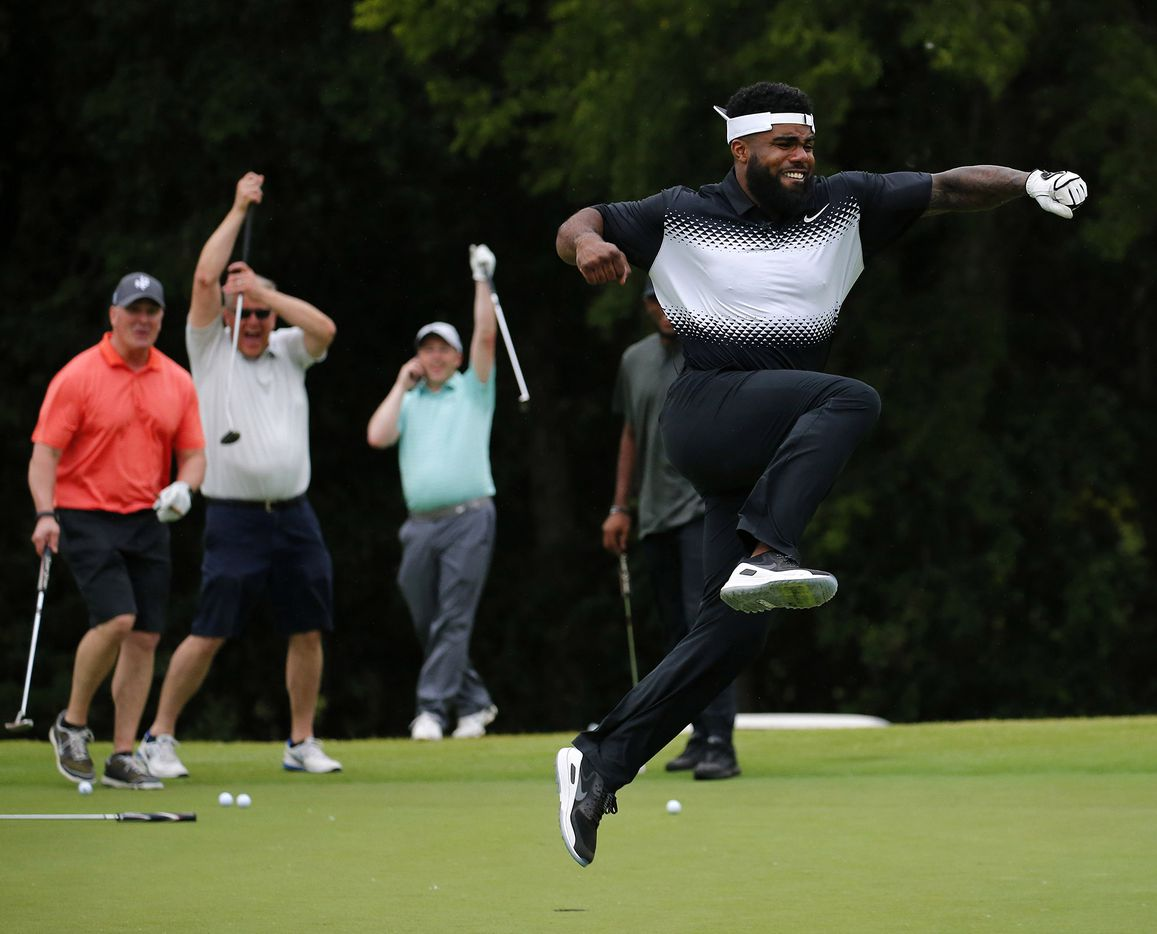 Cowboys running back Ezekiel Elliott celebrates his 25-foot putt, which banked off the back of a hole,  as playing partners from Albertsons cheer him on at the No. 10 hole during the Dallas Cowboys' Annual Sponsor Appreciation Golf Classic at the Cowboys Golf Club in Grapevine on May 10.