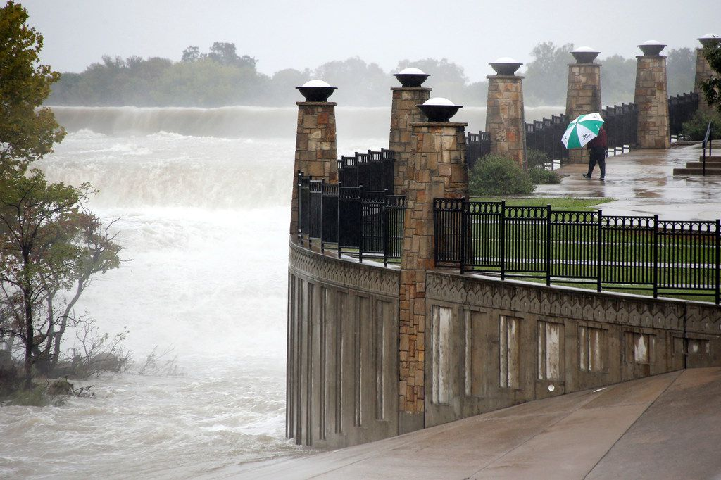 Bryan Alvizures of Garland walksby the White Rock Lake spillway in Dallas on Monday, October 15, 2018. People woke up to rainy weather and temperatures in the 40's.