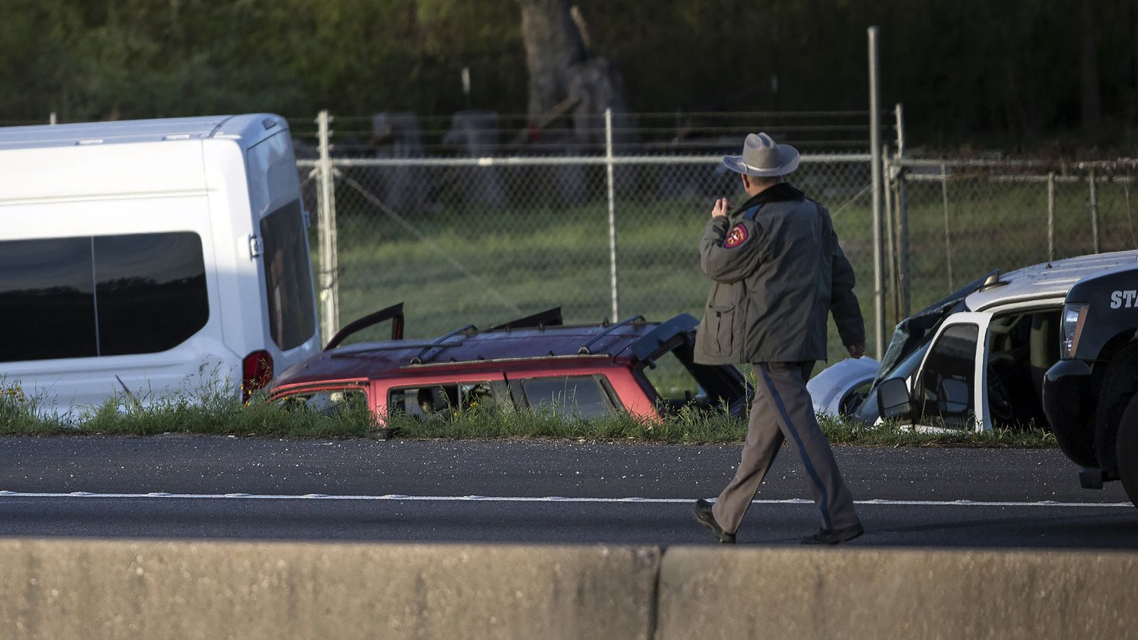 A Texas DPS trooper surveys the scene where authorities say Mark Anthony Conditt of Pflugerville, suspected in a series of bombings in Austin, killed himself by detonating a device in his vehicle as SWAT officers closed in to arrest him early Wednesday in Round Rock.