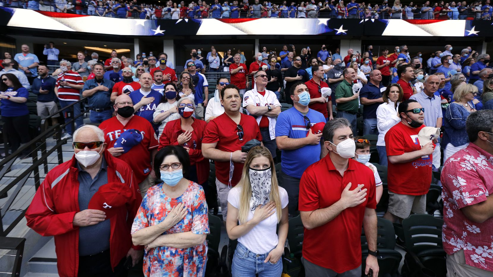 Texas Rangers fans (from left) Fred Aurbach, his girlfriend Leslie Lehman, his daughter-in-law Melissa Aurbach and son Wilson Aurbach and the rest of the nearly sold-out opening day crowd stand for the National anthem at Globe Life Field in Arlington, Monday, April 5, 2021. The Rangers were facing the Toronto Blue Jays in the home opener.