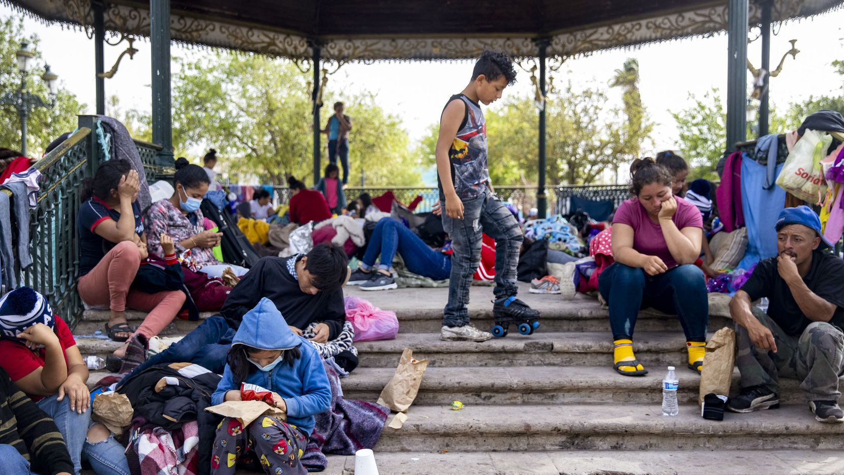 A young boy plays with a single roller-skate among other expelled migrants who sit around a gazebo in a public square in the Mexican border city of Reynosa on March 31, 2021. Migrants have resorted to living at the plaza as the U.S. continues to expel migrants under Title 42 — a pandemic-related public order still in place and left over from the Trump administration. (Lynda M. González/The Dallas Morning News)