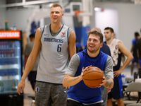 FILE - Mavericks guard Luka Doncic (77) prepares to shoot a 3-pointer as forward Kristaps Porzingis (6) watches during training camp practice at the team's practice facility in Dallas on Wednesday, Oct. 2, 2019.