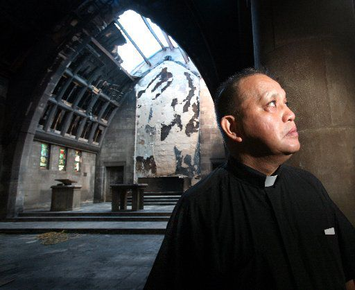 Edmundo Paredes stands in the charred remain of the sanctuary at St. Cecilia Catholic Church in Oak Cliff in 2007.