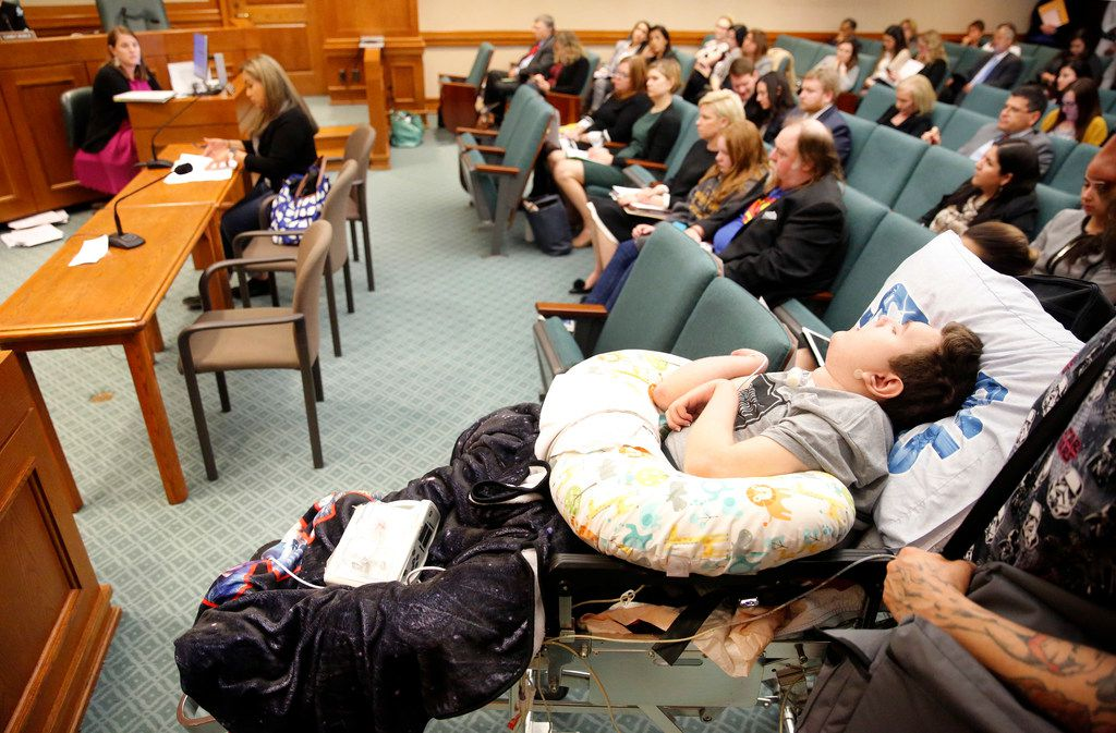 Bed-ridden Briar McCann, 15, listens to his mother Gabriella McCann (left) of Bulverde, Texas testify on House Bill 2453 during a House Human Services Committee meeting.