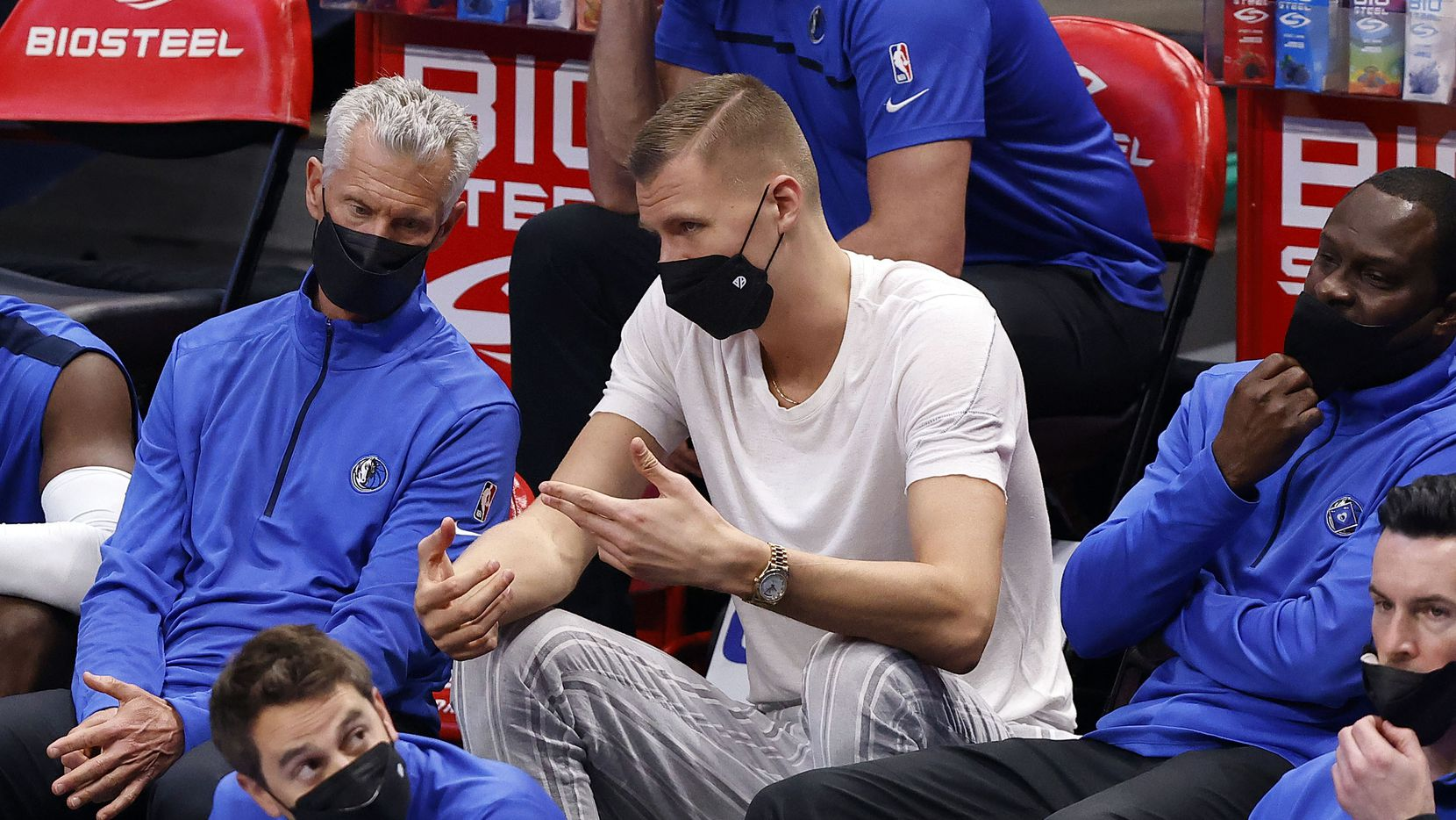 Injured Dallas Mavericks center Kristaps Porzingis (right) visits with coaches on the bench during their game with the Cleveland Cavaliers at the American Airlines Center in Dallas, Friday, May 7, 2021. The Mavericks blew out the Cavs, 110-90.