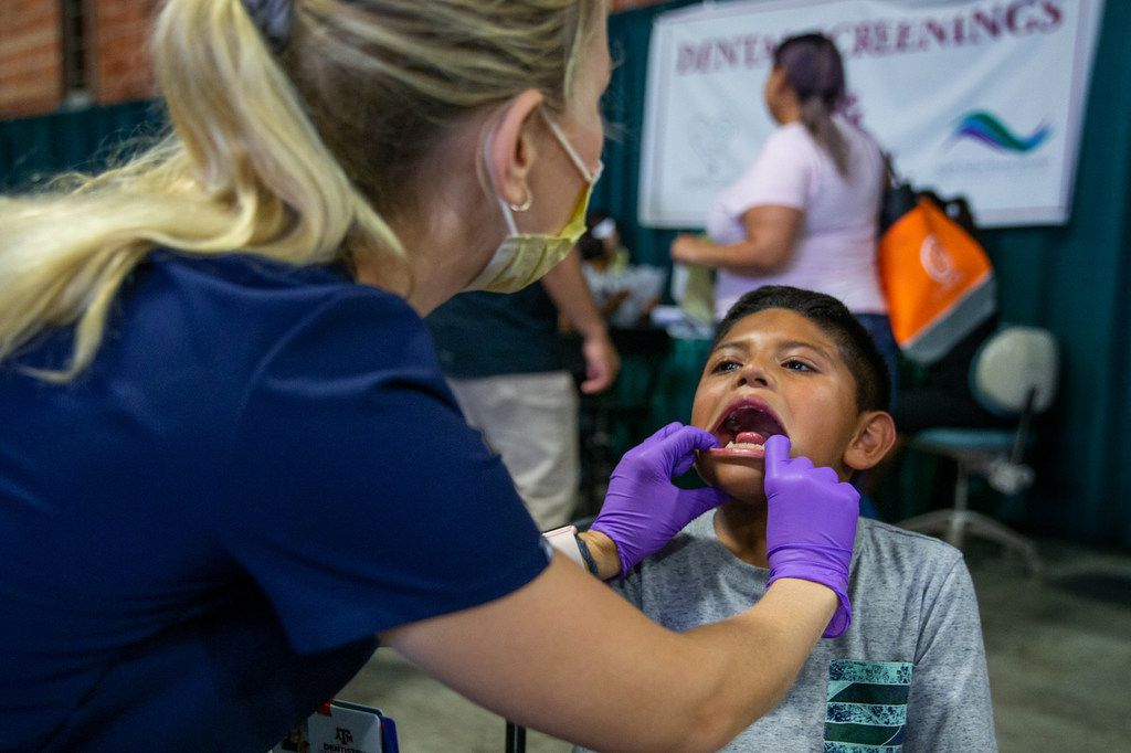 Joshua Hernandez, 7, receives a dental screening during the 23rd annual Mayor's Back to School Fair at the Fair Park Centennial Hall in Dallas on Friday, Aug. 2, 2019. Thousands of children and their family members were expected to attend, and the event included health and eye screenings, dental screenings, backpack giveaways and more.