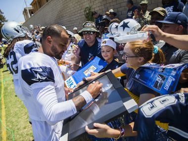 Dallas Cowboys quarterback Dak Prescott (4) signs autographs for fans during a morning practice at training camp in Oxnard, California on Thursday, August 8, 2019.