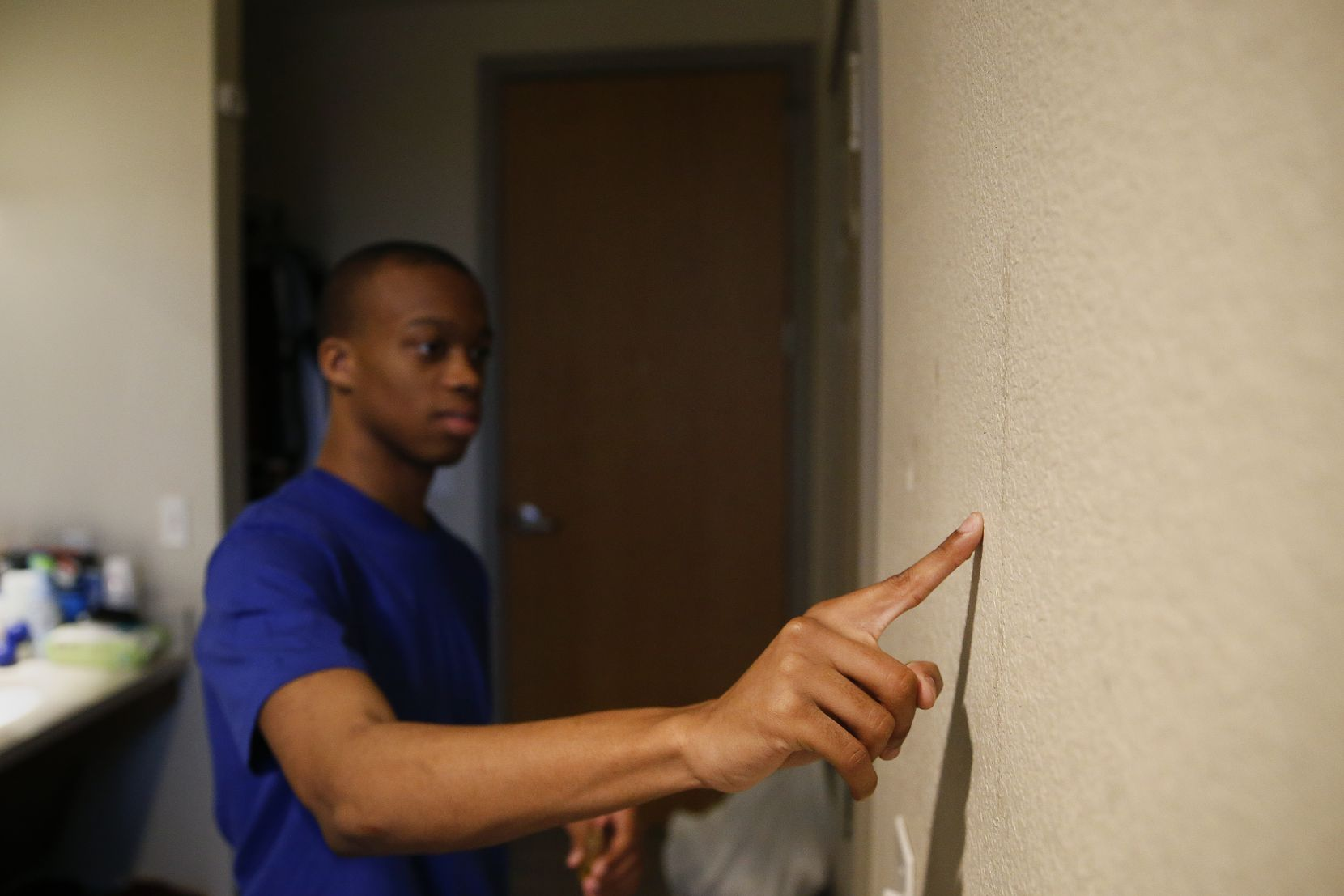 """Using anointed oil, Jaylon Miller makes the sign of the cross on the wall of his dorm room as a sign of God's protection at UNT-Dallas. """"It's something my mom taught me,"""" Miller said. """"I put a symbol of the cross on the wall for protection. Another cross on my forehead to keep my mind protected. You know, to keep anything from going in or out that isn't of God."""""""
