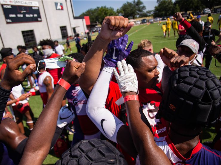 Players from the Team Grind Black from Dallas huddle with coach Derrick Williams after beating the Iconic team in the Pylon 7-on-7 tournament at the A+D1 field on Aug. 1, 2020 in Carrollton. Grind won against Iconic, 35-28.