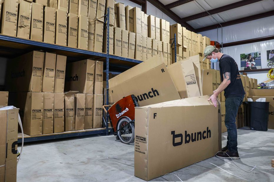 Logan Holland opens a bike box at Bunch Bikes in Denton on Wednesday, March 24, 2021. (Lola Gomez/The Dallas Morning News)