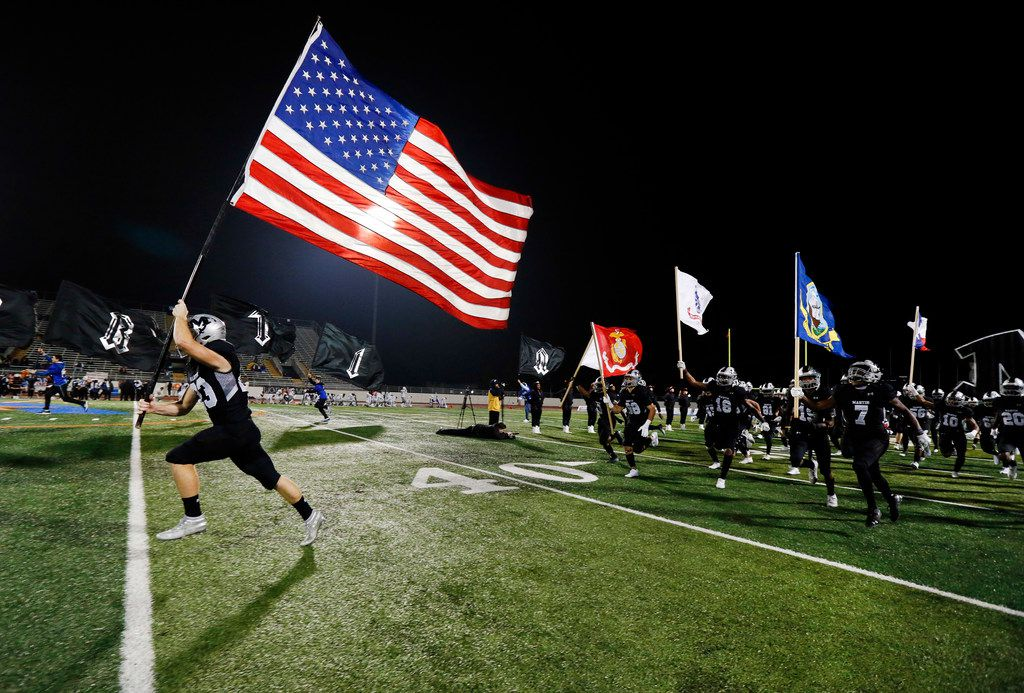 Martin High running back Jacob Colburn (23) carries the U.S. fly as his teammates carries the branches of the military flags onto the field before facing Bowie at Maverick Stadium in Arlington, Texas, Thursday, November 7, 2019. (Tom Fox/The Dallas Morning News)
