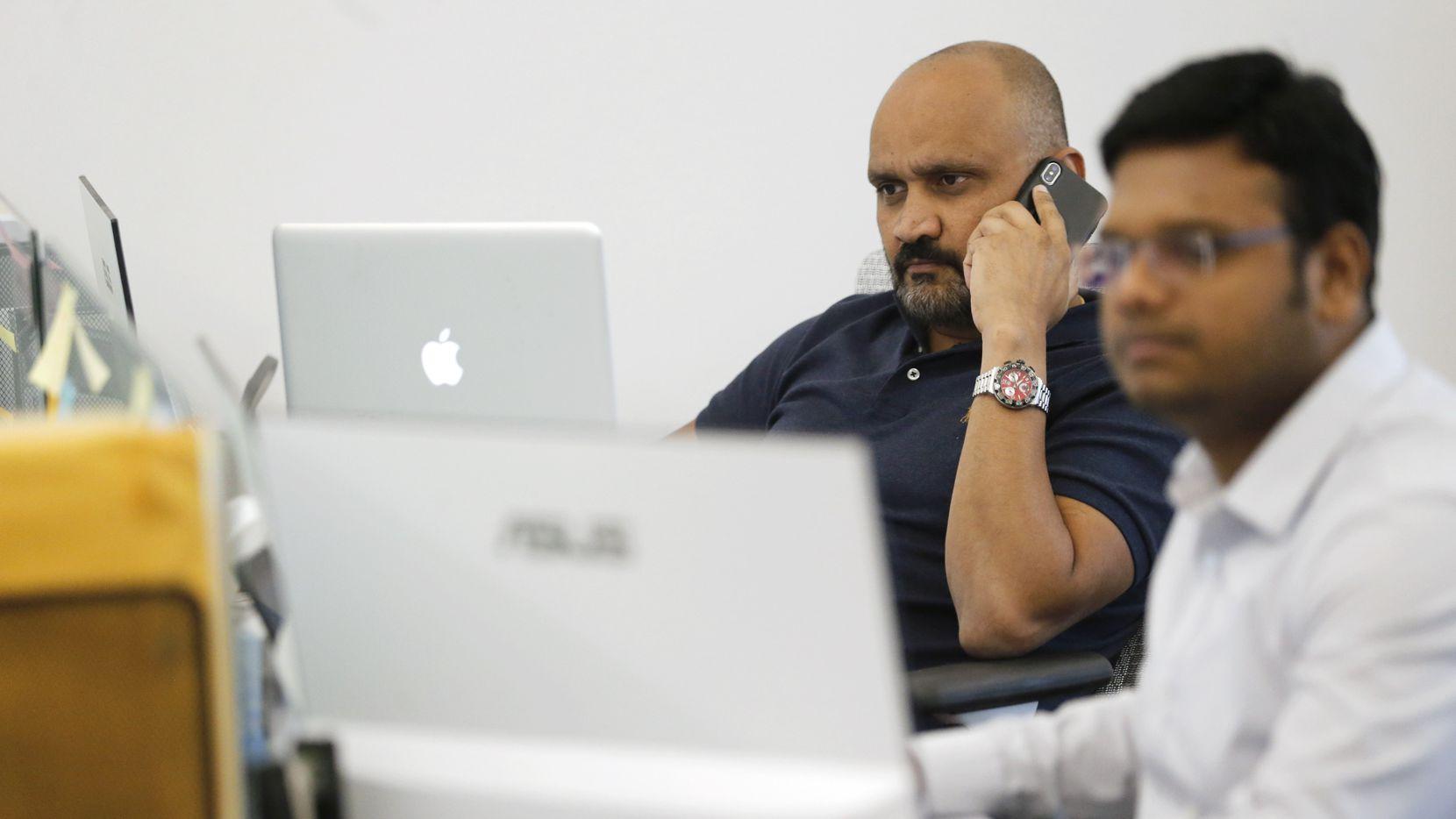 Nash Singi (left) worked from his desk next to Vikram Vunduru (right) at Qentelli in September.