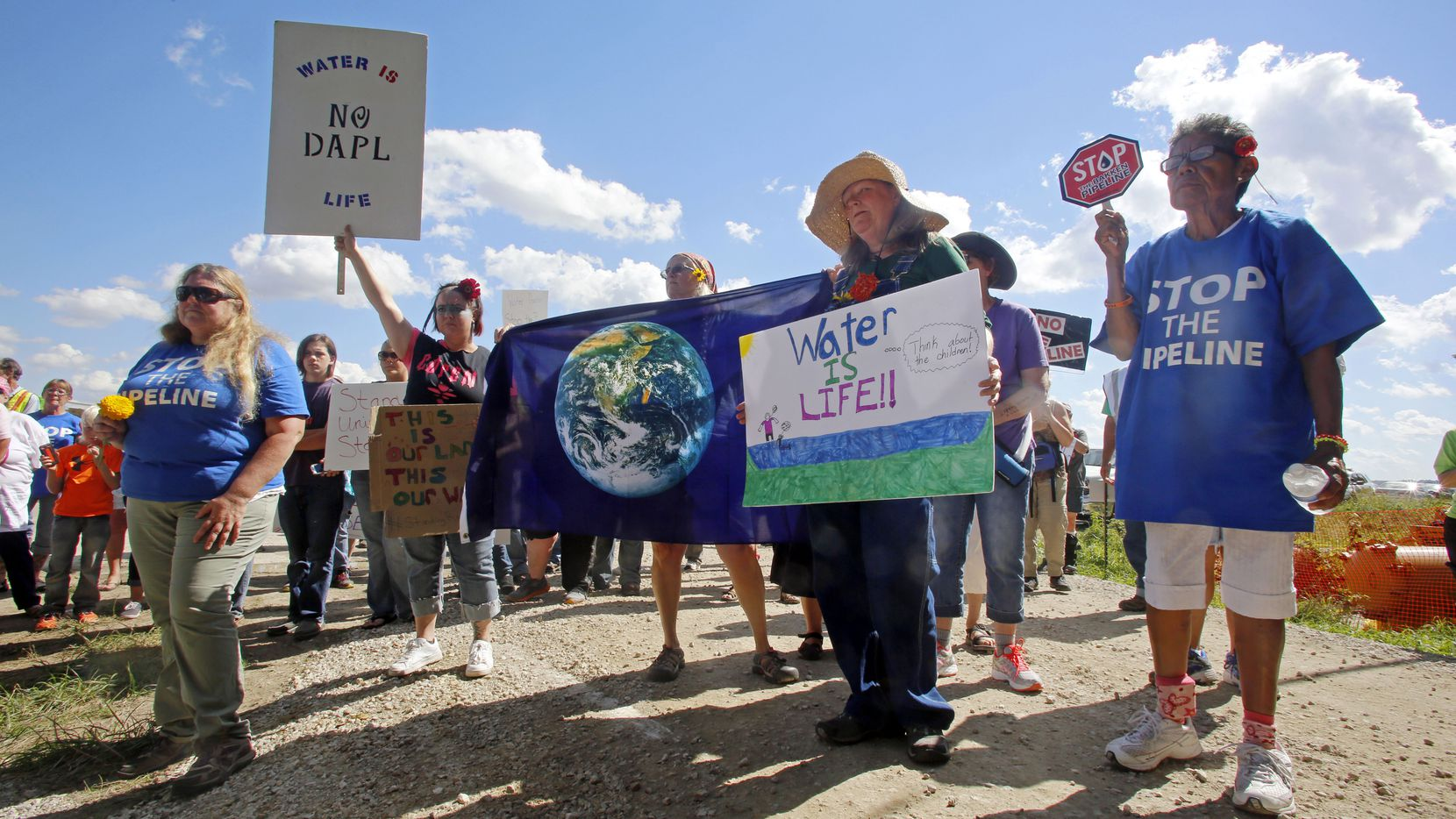 A group of people hold signs as they prepare to trespass into a Dakota Access Pipeline construction site during a protest which took place at a pipeline construction site Saturday, Sept. 17, 2016, in Montrose, Iowa. (Erin Lefevre/The Hawk Eye via AP)