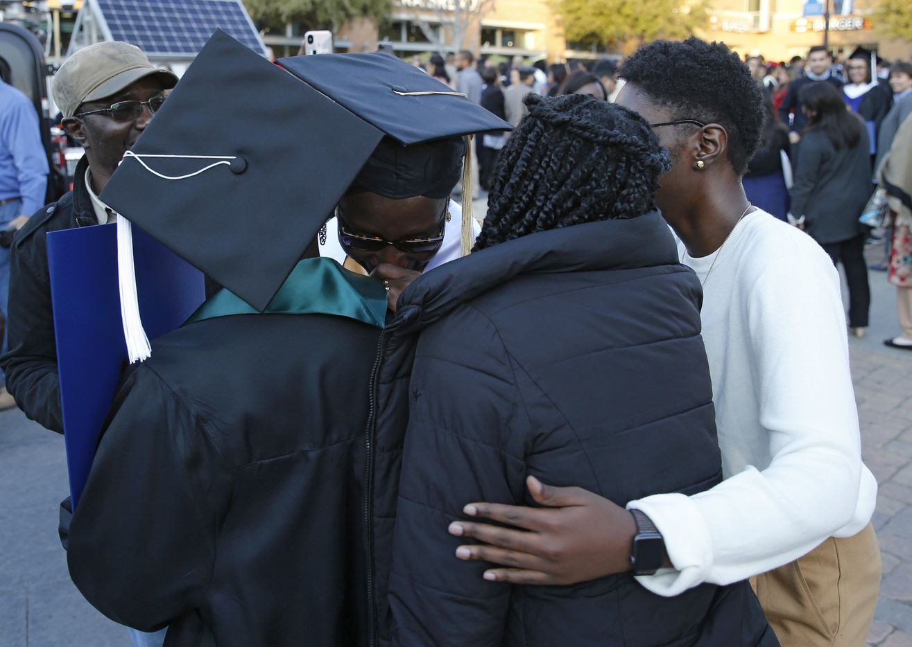 Ndeye Ndaw (center) gets emotional as her three daughters hug her after she and Awa Sy, her oldest, graduated from the University of Texas at Arlington on the same day.
