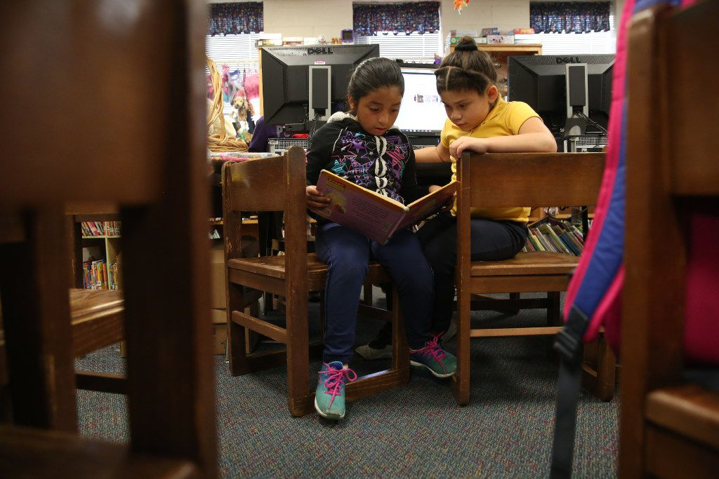 Second-grader Valerie Tovar (left) and first-grader Carla Chavez read a book in the library after school at B.H. Macon Elementary School in Dallas in 2016. Dallas ISD launched a program to boost reading ability for English-language learners and African-American students before the start of the 2018-19 school year, and early returns are promising.