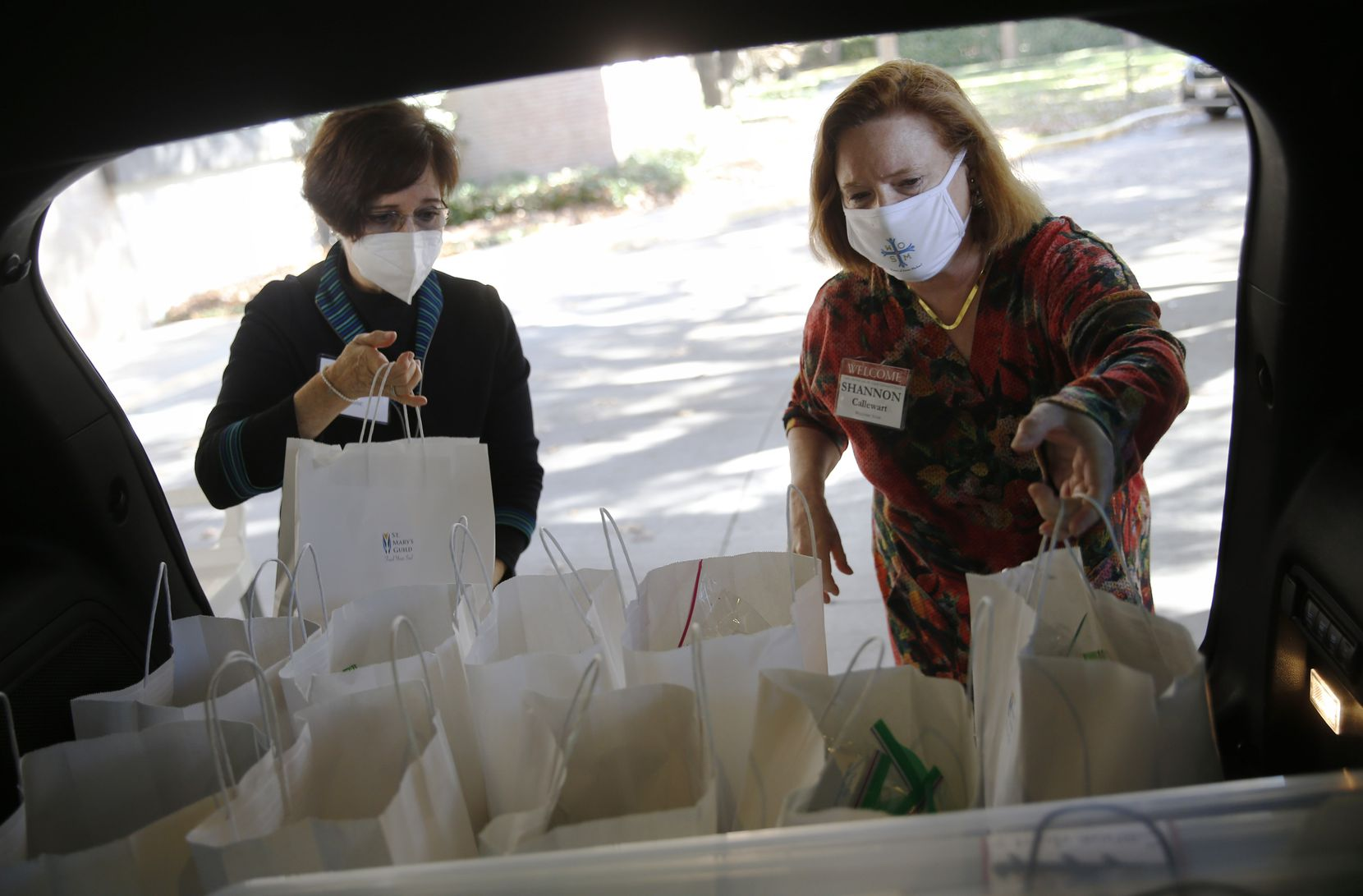 Paula Calise (left) and Shannon Callewart load Shannon's vehicle with baked goods to be delivered to Baylor University Medical Center.