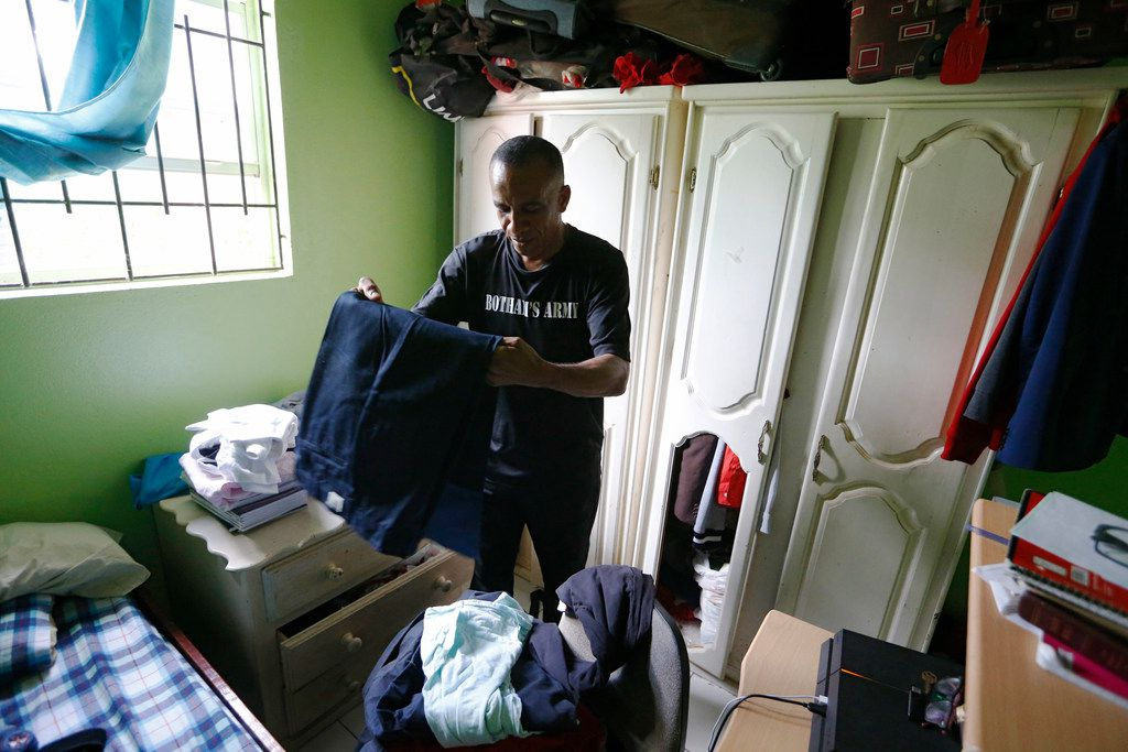 Bertrum Jean sorts through clothes that Botham Jean kept in the closet of his childhood bedroom in St. Lucia.