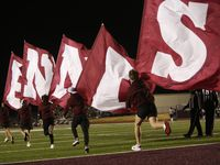 Ennis Lions supporters race onto the field with flags following one of the team's first half touchdowns during their game against Frisco Liberty. The two teams played their Class 5A Division ll  bi-district round playoff football game at Lion Memorial Stadium in Ennis on December 11, 2020.
