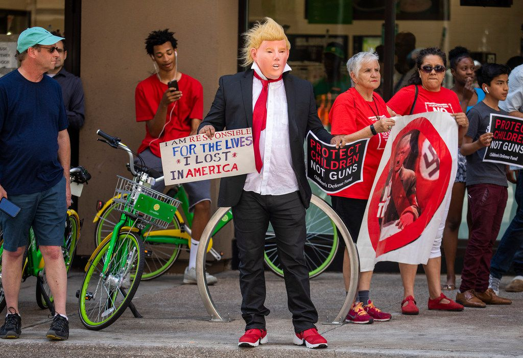 Protestors gather on Commerce Street awaiting the arrival of President Donald Trump's motorcade to The Adolphus Hotel for a fundraiser on Thursday, May 31, 2018, in Dallas. (Smiley N. Pool/The Dallas Morning News)