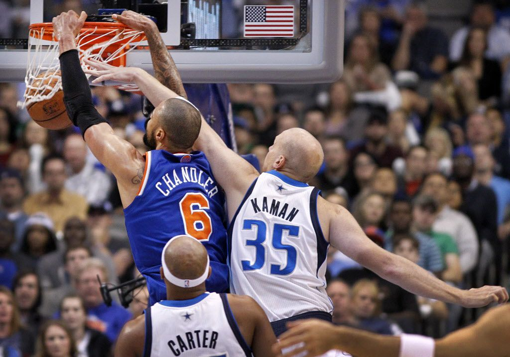 with Dallas Mavericks center Chris Kaman (35) on his back, New York Knicks center Tyson Chandler (6) goes to the basekt for a dunk  in the first half at the American Airlines Center in Dallas, Wednesday, November 21, 2012.  (Tom Fox/The Dallas Morning News)