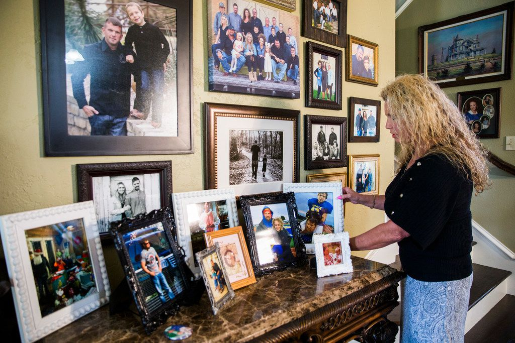 Diane Wallace rearranges framed photos of her son, Andy DeBusk, at her home. She said she regrets not bailing out her  son when he called on Christmas Eve 2016 from the Parker County jail.